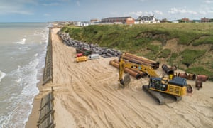 Sandscaping in Bacton with diggers on coastline.