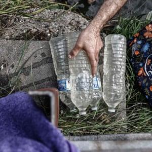 Falah fills water bottles from a river
