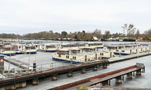 Kormoran boats lie in icy water at the dock from the houseboat rental company Kuhnle Tours on lake Claassee near Rechlin, Germany.