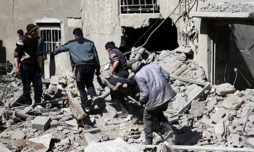 A body is carried on a stretcher through the rubble of damaged buildings in the rebel-held besieged town of Hamouriyeh, eastern Ghouta