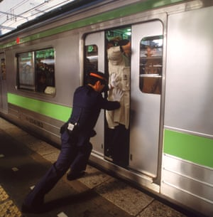 A 'pusher' squeezes people on to a Tokyo metro train.