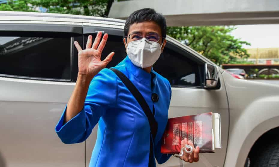 Philippine journalist Maria Ressa waves to members of the media after attending a court hearing in Manila on on charges of tax evasion