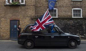 A London Black taxi driver flies a British flag as he drives through a street in central London