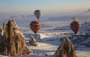 Cappadocia, Turkey: Hot-air balloons glide above snow-covered fairy chimneys in the historical Cappadocia region in Central Anatolia's Nevşehir province