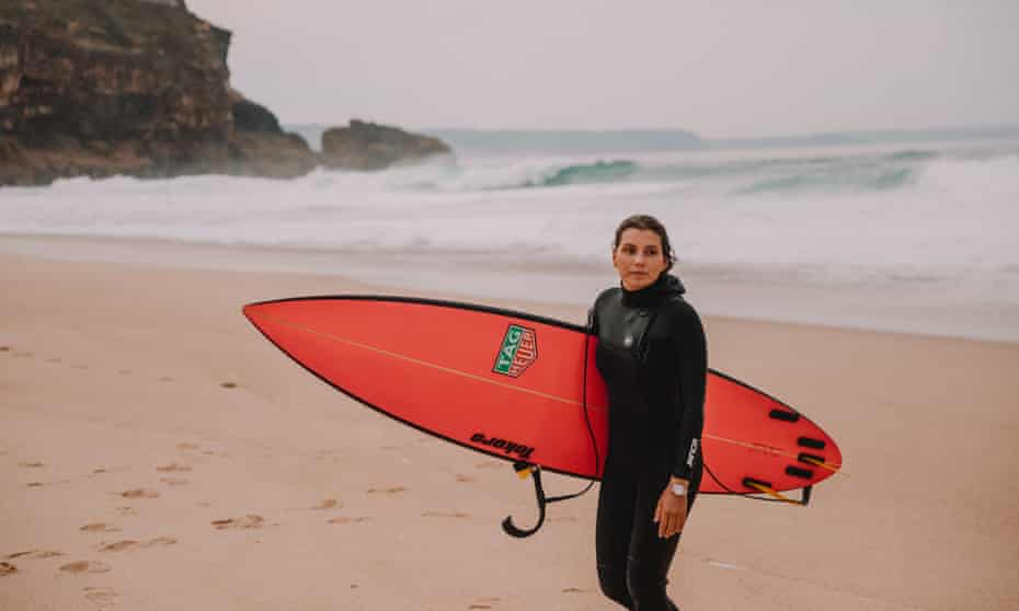 Maya Gabeira in her wetsuit, carrying her surfboard on a beach