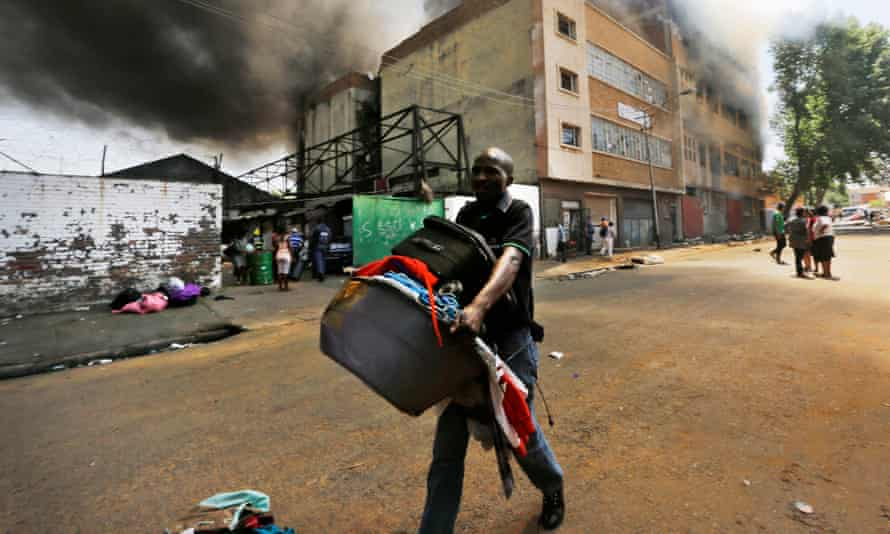 A recently evicted man runs away carrying his belongings as a warehouse burns in central Johannesburg