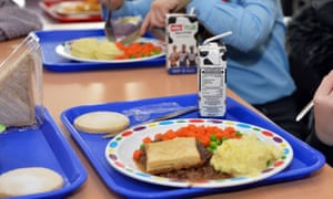 Picture of school meal - looks like cottage pie with carrots and peas - on a blue tray with young children, cropped so as not to reveal their faces.