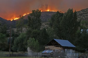 Flames and smoke rise on a ridge line above a ranch