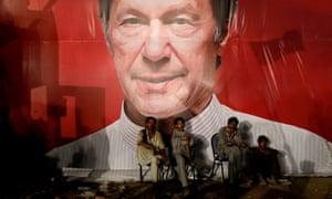 Labourers sit under billboard of Imran Khan.