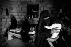 Adeeyah Abdo Alwan, 39, with her daughter inside her temporary home in Enma, Aden