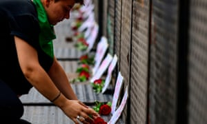 A woman lays a rose in honor of a victim of femicide outside the presidential palace in Buenos Aires, Argentina.