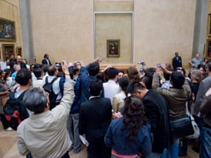 Tourists photographing the Mona Lisa at the Louvre.