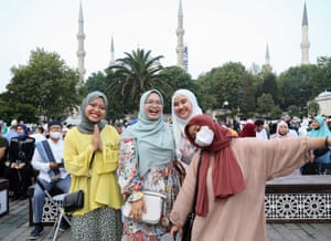 Muslims pose for a photo at Sultanahmet Square after performing Eid al-Adha prayer at Hagia Sophia Grand Mosque in Istanbul