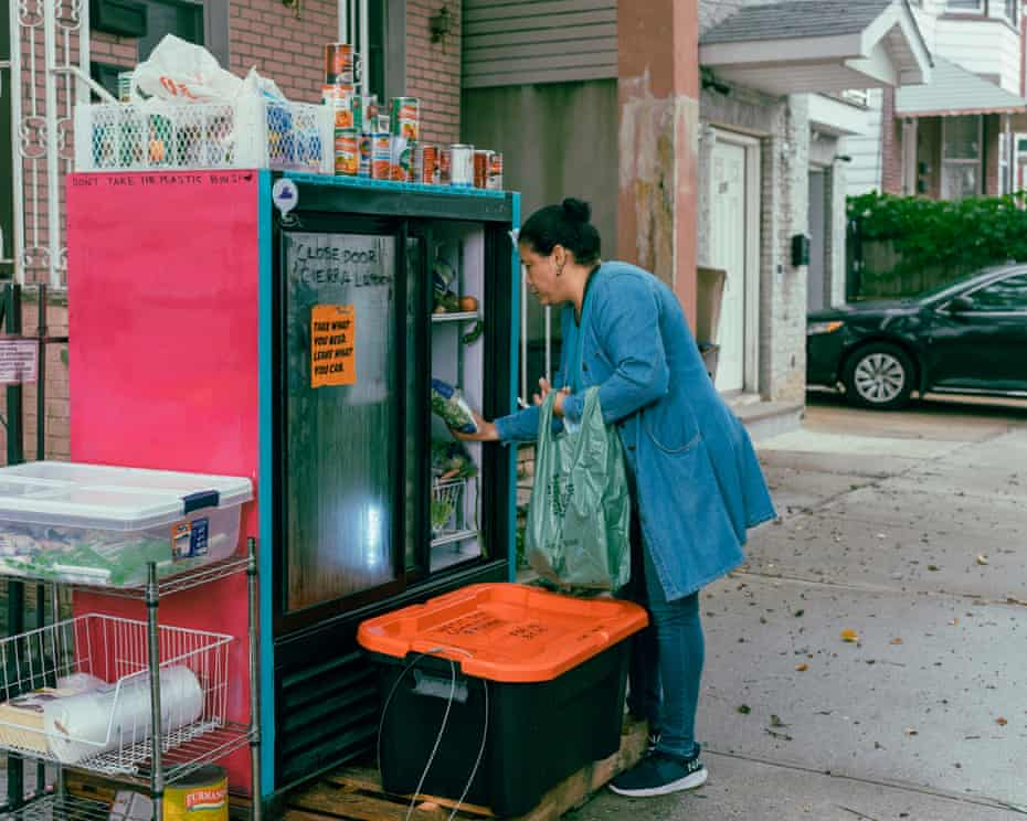 A woman gets food from the communal refrigerator in front of Smith's house in Jersey City.