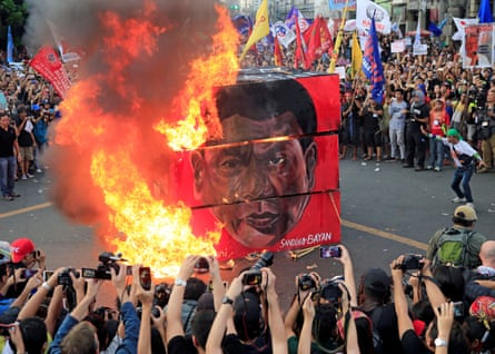 Protesters burn a cube effigy with a face of President Rodrigo Duterte during a National Day of Protest in Manila on 21 September.