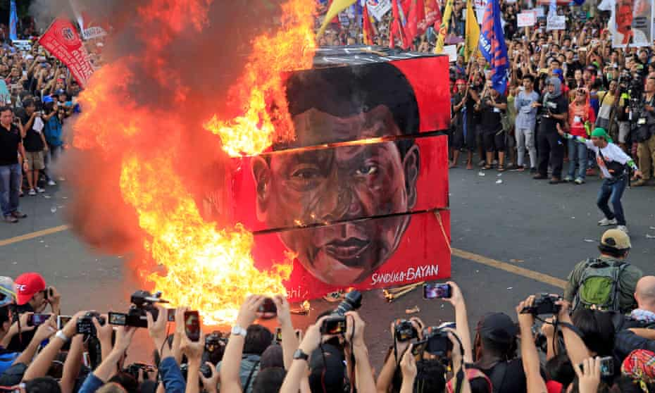 Protesters burn a cube with the face of Rodrigo Duterte during a national day of protest.