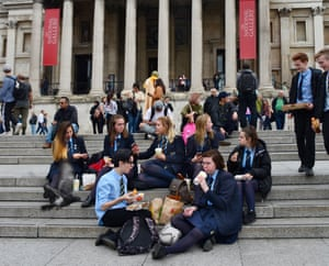 A group of British school students eat lunch on the steps of the National Gallery in London, England