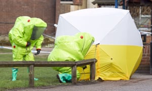 Personnel in hazmat suits securing a tent covering a bench in the Maltings shopping centre in Salisbury.