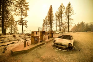 A burned-out car and petrol station after wildfires in Paradise, US