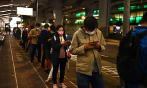 Commuters wear protective masks to prevent the spread of the coronavirus disease while waiting for a bus in Taipei.