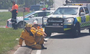 Firefighters take a break from working to contain a bushfire