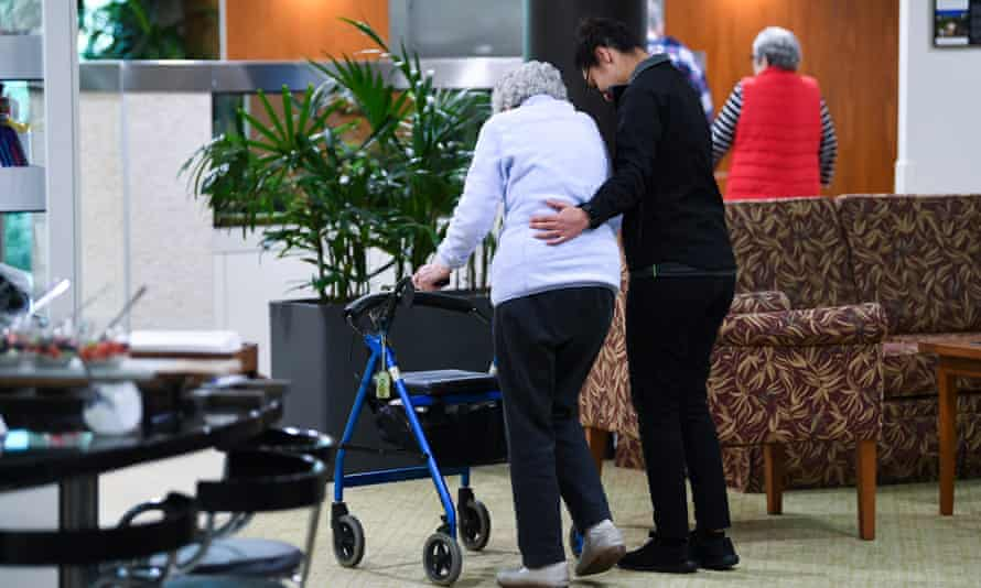 An aged care resident being helped by an aged care worker.