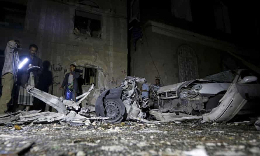 Police officers inspect the site of the car bomb attack in Yemen's capital Sanaa.