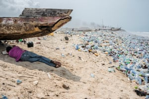 Accra, Ghana: A man takes a rest in the shade on a litter-strewn beach close to Africa's biggest electronic waste disposal site