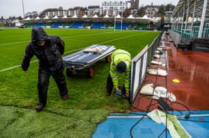 Scotstoun Stadium grounds staff remove the perimeter advertisements following the cancellation of the Glasgow Warriors v Leinster game, due to the weather conditions.