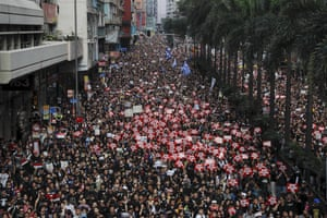 Tens of thousands of protesters carry posters and banners march through the streets