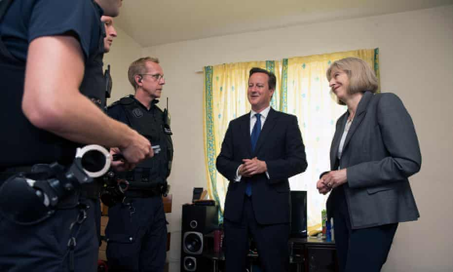 David Cameron, then UK prime minister, and Theresa May, then home secretary, with Home Office officers in 2014 at a house where several migrants were arrested in Berkshire.