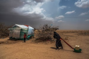 An elderly woman drags water back to tent at Abs IDP camp, Yemen, May 2017
