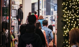 Shoppers wearing face masks enter the David Jones store after the doors were officially opened for the Boxing Day sales on 26 December 2020 in Sydney.
