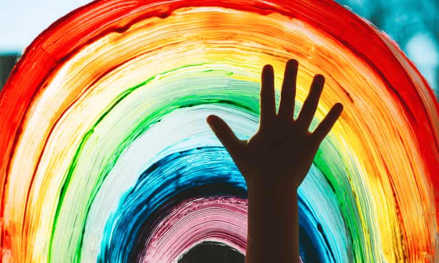 child's hand in front of painted rainbow