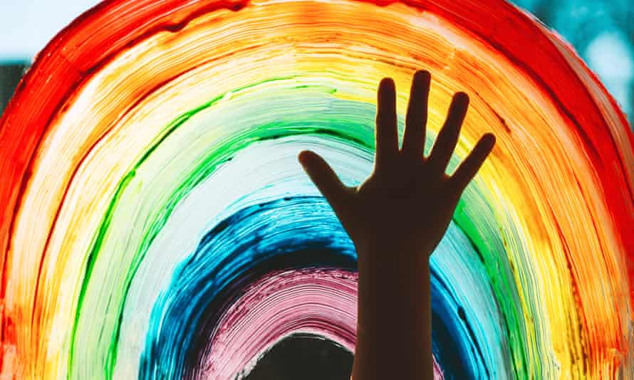 Close-up photo of child's hands touching a painting of a rainbow on window.