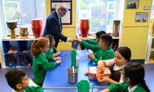 Tim Roach, a vice-principal, wears a face shield as he supervises year 4 children during their lunch break, at Greenacres primary academy in Oldham, northern England. Photograph by Oli Scarff/AFP/Getty