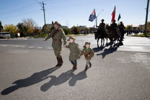 Jason Stevens leads his children Brooke 6, and Clay 4, all members of the Murrumburrah Light Horse re-enctment troop across the highway as they march towards the cenotaph.