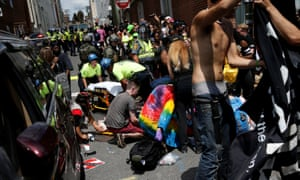 Rescue workers assist people who were injured when a car drove through a group people at the rally.