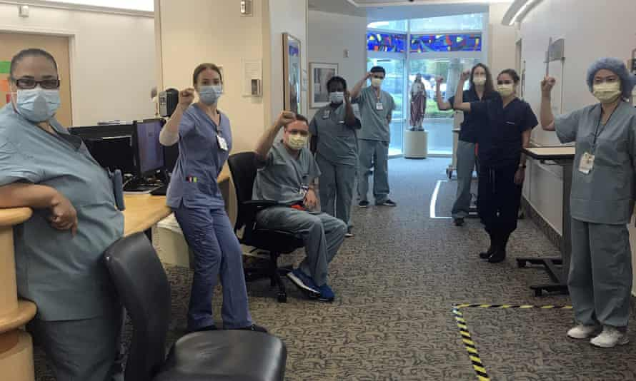 Nurses at Providence Saint John's health center in Santa Monica raise their fists in solidarity after telling managers they can't care for coronavirus patients without N95 masks.
