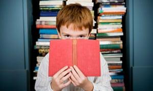 boy's eyes looking over top of book