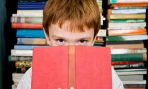 A boy peers over the top of a book