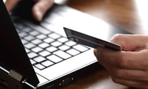 Laptop keyboard and hand holding debit/credit card