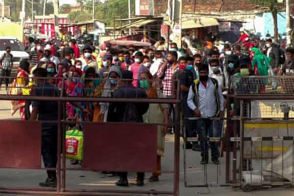 Nepalese migrant workers wait to cross the border