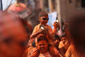 A boy plays the cymbals while sitting on his father's shoulders