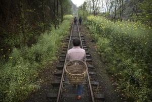 Villagers walk on the rail tracks in Bagou