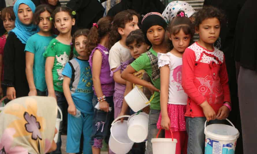 Syrian children wait to receive food in the rebel-held side of Aleppo