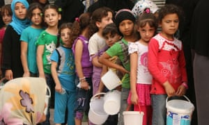 Syrian children queue up to receive food aid food in Aleppo, September 2015