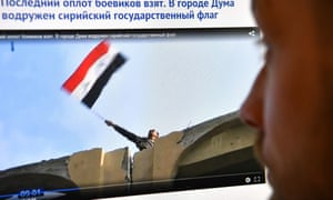 A screengrab from a video aired on Russian media shows a man reportedly waving a Syrian flag from a building in Douma.