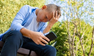 Teenage boy texting on phone