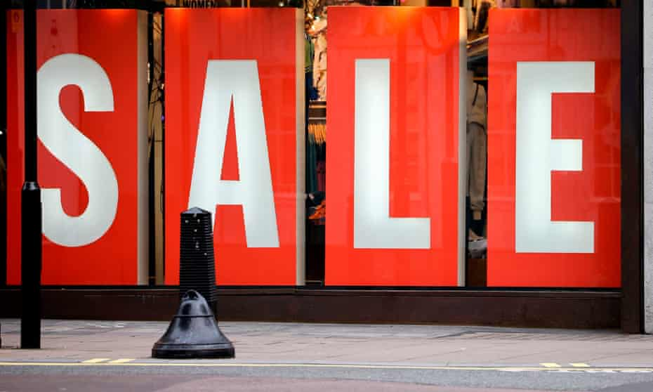 A giant sale sign in the window display of a shop